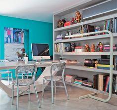 """Peça de cimento. Durante a reforma de sua casa em São Paulo, o arquiteto se deparou com o pilar metálico que sustenta a escada de acesso ao 2o and. Resolveu ocultá-lo projetando uma estante de 2,46 m de altura, composta de chapas de drywall revestidas de microcimento, material impermeável também usado no piso. Apoio à mesa de uso misto: trabalho e jantar. """"Nichos, com alturas entre 34 e 50 cm, e consegui até disfarçar, no mais alto, o ar-condicionado."""""""