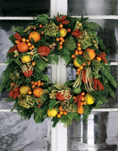 A cedar wreath adorned with oranges, lemons, kumquats and limes provides visual impact and recalls the Victorian Christmas tradition of indulging in exotic fruit. Dried hydrangea blooms, salal leaves and amaranthus add texture to the monochromatic backdrop, allowing the oranges and yellows to take centre stage.