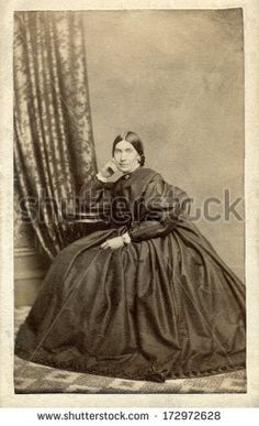 CIRCA 1861 - A vintage Cartes de visite photo of beautiful pioneer woman sitting in chair. She is dressed in hoop skirt dress. Photo from the Civil War Victorian era. A digital copy of this photo can be purchased at the above web link.