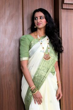 Accessoried with traditional temple jewellery for a cream bengal cotton sari