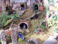 The Smurfs have invaded our Fairy Garden display...You will find a tent complete with picnic table and fire, a bridge over a stream, fairy caves, and other items for your gardening fun...Soon the fairies will return and the Smurfs will be run out of Fairy Land!