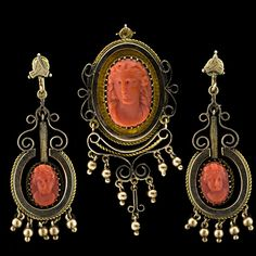 Suite of a pin and matching earrings from the Victorian time period. Carved coral cameos of a lady in profile are set with delicate pointed prongs inside ornate frames with bead fringe and scroll work detailing.