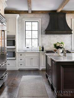 white kitchen cabinets. white marble countertops. black/dark brown kitchen island. black/dark brown range hood. white marble backsplash