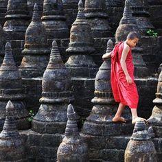 Monk walking across stupas that form a Buddist temple, Burma.