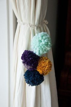 make your own pom pom curtain tie back...how to...love this for a kid's room...