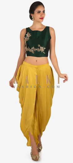 Buy Online from the link below. We ship worldwide Click Anywhere to Tag Dark green and yellow dhoti suit enhanced in zardosi embroidered work only on Kalki  Dance away the night at your besties sangeet ceremony in this dhoti suit. The crop top in raw silk is featured in dark green. It is intricately constructed using the zardosi floral motif embroidery work. Matched with a yellow dhoti in satin with a front zip opening. Slight variation in color is possible.