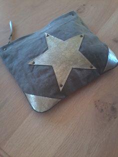 Pochette main plate pour sortir ou pour les sac Matière :Elle est coupée dans une toile kaki de l'armée française des années 50/60, les angles, le motif central ainsi que la patte zippée sont en cuir doré, quelques rivets animent l'étoile.