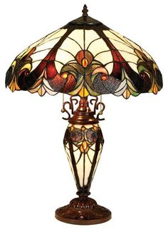 Add this cozy Victorian-style table lamp to any room for instant character and ambiance. This two-bulb lamp features a lighted glass-work base that complements the Tiffany-style stained glass shade. T