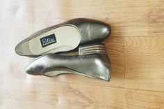 Silver leather shoes with gold striped trim flat heels, rounded toe. LABEL: Bellini Made in New Zealand MEASUREMENTS: Inside Sole (from toe to heel): 25.5cm Inside Sole (widest part):8cm Few scratches, nothing major. In good condition. *Please bear in mind that colours on the photo may slightly be different from actual item colours * Please note that these are vintage clothing, and they may have slight signs of wear. We try our best to examine each piece and will write in note about holes...