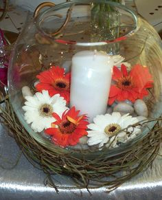 Elegant fish bowl with gerbera daisies and a pillar candle resting upon a whicker nest for a wedding centrepiece