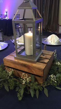 Lantern centerpieces on a wood box with greenery