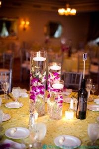 Centerpieces with cream candles, crystal marbles and purple & white dendrobium orchids.