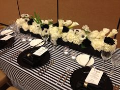 Floral centerpiece fit for a gala! Featuring  black succulents, black-eyed anemones & swooped calla lilies. Long box wrapped in black silk fabric.