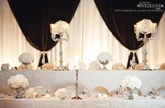 white and silver head table set up bride and groom in the back, higher up, parents and siblings in the front a little lower