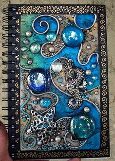 I covered it with a sheet of black Fimo, cut holes in the clay where the glass gems si. Polymer clay on acrylic tile Journal Covers, Art Journal Pages, Art Journals, Blank Journal, Fimo Polymer Clay, Diy Fimo, Metal Embossing, Paperclay, Handmade Books