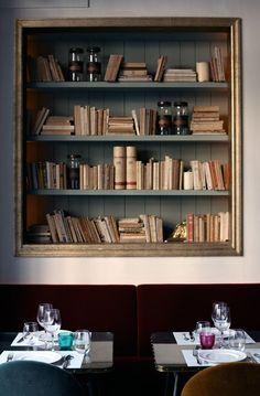 Cafe Kafka in Barcelona, 1950's retro pendants in historical building. A bookshelf filled with classics is surrounded by a gold frame. | Remodelista