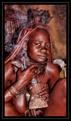 Africa | Himba woman 'applying' perfume.  Kaokoland, Namibia | ©Jessi van Dijck | The Himba women of northern Namibia perform daily rituals in which they anoint themselves with a mixture of ochre, oil, and ash to protect themselves from the harsh desert climate. They never take a shower, but rather burn aromatic herbs in a pot each morning with which they smoke themselves as if applying perfume.
