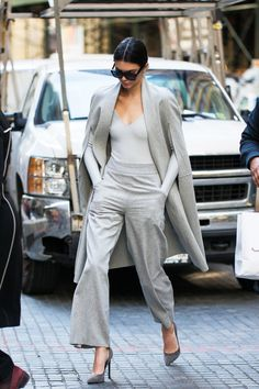 Kendall Jenner wears grey head to toe with a bodysuit, flared trousers, a cape coat, and pointed pumps