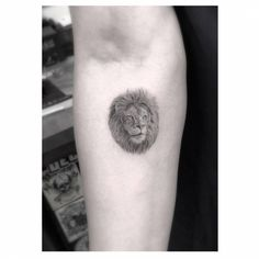 Fine line style lion portrait tattoo on the right forearm.