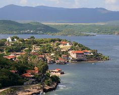 """Santiago de Cuba Bay. In the middle of the picture we can see """"Cayo Smith"""", small rocky island in the center that serves as settlement of fishermen. In the background we can see The Sierra Maestra foothills that served as a shelter and refugee of a group of revolutionaries leaded by Fidel Castro 1958 - 1959"""