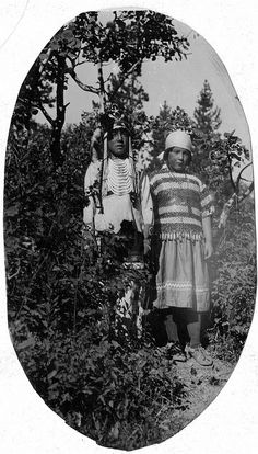 Native American male and female standing on mound in front of trees and bushes