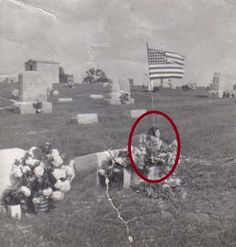 This old photo, some claim has a ghost in it? It is said that there is a young girl allegedly sitting by her own grave. Could it be paranormal our just a very good case of pareidolia and the girl is just the flowers? You decide.  I clearly see a face/head that is transparent and you can see the flagpole through her.   Agree?
