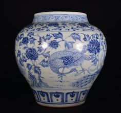 LARGE BLUE AND WHITE JAR. The vase is wide-globular shaped. The exterior is decorated with peacocks surrounded by blooming flowers and leaves. 14 1/8 in. tall. Ming Dynasty