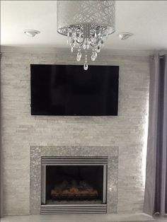 Modern / Contemporary White quartz ledger stone fireplace. Anatolia Glacier, starfire glass, stainless steel surround, chandelier, flat screen tv over fireplace, white marble floor, gray carpet and drapes, can lights