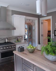 The kitchen walls are painted in Sherwin Williams Warm Stone 7032, which is a warm contrast behind the white cabinetry.  This color is a nice grayed brown.