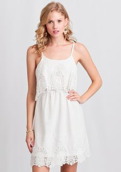 This stunning white cotton frock features a scalloped lace hemline and tiered bodice with embroidered details.