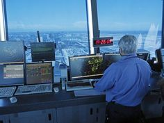 An air traffic controller works at computer screens and a digital clock in the tower at Los Angeles International Airport. (Photo: Reed Saxo...