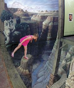 "This June 15, 2012 photo released by the National Geographic Visitor Center at Grand Canyon shows an unidentified visitor examining the sidewalk artwork ""Grand Canyon Illusion"" by artist Kurt Wenner o"