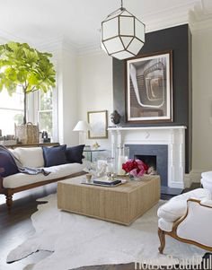 Neutral and Natural Living Room    Antique meets modern in the living room of a San Francisco Victorian. Designer Ken Fulk chose a black and white palette, softened with neutrals and natural textures. The chimney breast is papered with Ralph Lauren's black Yacare Crocodile, and a Ralph Lauren Peyton ottoman sits on a cowhide rug from Frank's Leather & Hides.