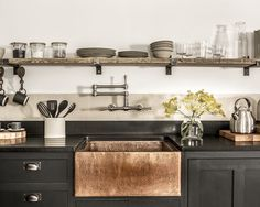 Small industrial l-shaped kitchen idea in Cornwall with a farmhouse sink, black cabinets, granite countertops, cement tile backsplash and open cabinets