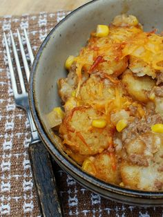Cowboy Casserole  adapted from a recipe at Taste of Home  1 1/2 pounds ground beef, 1 medium onion, chopped  3 cloves garlic, chopped  1 can (15.25oz) whole kernel corn, drained  1 can condensed cream of mushroom soup  2 cups cheddar cheese, shredded  1/2 cup milk  4 tablespoons sour cream  1 bag (30 oz) frozen tater tots (used Ore-Ida Crispy Crowns)