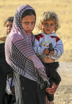 A Syrian woman holds a child in her arms as they cross into Turkey via the border in the Akcakale district of Sanliurfa on June 6, 2015.