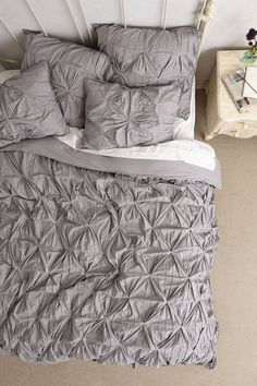 I would do this bedding with a lovely, large black lacquered headboard, a glass bedstand and silver lamp with a deep purple shade. Toss in a teal cashmere throw at the foot of the bed and it's done!