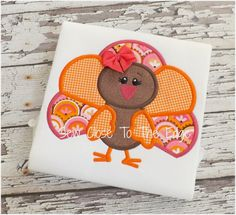 An adorable girly girl turkey in pinks and oranges with a sweet little bow. Appliqued with designer fabrics on a 100% cotton short sleeve