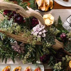 A holiday centerpiece on a table at Rebecca Minkoff's Brooklyn home.  A centerpiece made with succulents, eucalyptus, and driftwood dominates the table.