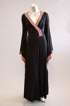 An Alice Pollock moss crepe over-dress, early 1970s, labelled and size 8, with side fastening at waist, wide kosode-like sleeves edged in mauve crepe which fall in gothic points, bust 86cm, 34in, waist 66cm, 26in