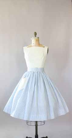 Vintage 50s white eyelet cotton dress with light blue pin striped skirt. Matching waist belt. Adorable eyelet heart pocket on skirt. Metal zipper up back. Bodice fully lined. Amazing quality, crisp cotton on skirt. Crinoline worn underneath skirt in photos for added fullness. Very good vintage condition- zipper is in working order it just wouldnt zip all the way up my dress form because the dress was too tight. This piece has been cleaned and is ready to wear! Label Julie Miller Fabric…