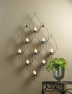 """Candleholders & Candles Home Locomotion Iron and candlelight combine to make a plain wall truly spectacular. The artistic curved iron frame features 9 candle platforms and easy-mount brackets. Candles not included. Item weight: 4.00lbsItem dimensions: 3.00"""" W x 36.75"""" H x 22.63"""" LMaterials: IronUPC: 849179022129"""