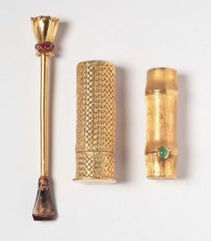 A cigarette holder and two gold lipstik case