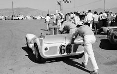 Jim Hall's Chaparral 2C is pushed by crew members in the Riverside paddock. This event, the famous Los Angeles Time Grand Prix, still drew the best of the best every year. Hall was on the front row, but the crew discovered a broken spherical bearing in the rear suspension too late to fix it for the race. Sharp would win in his flipper equipped Chaparral 2. Al Bochroch photo.
