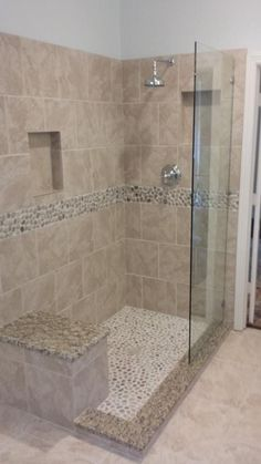 Doorless Shower with river rock floor, rain showerhead, river rock deco band creates a very therapeutic environment in this bathroom.