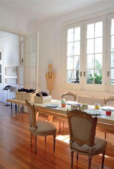 La conjunción de elementos contemporáneos y la arquitectura francesa refuerzan el clima teatral e íntimo del comedor. La espectacular mesa de álamo de 4,50 m (diseño de Oropel) contrasta con las sillas francesas tapizadas en lino color piedra. Junto a la ventana, un maniquí de MDF que luce un collar africano custodia la escena.