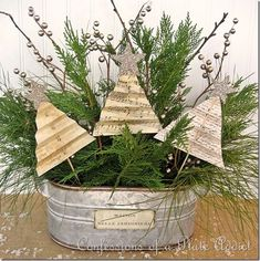 Old book pages repurposed into simple but elegant Christmas decorations planted into a galvanized wash tub filled with live greens. Simply charming.
