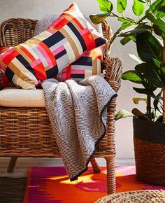 Fauteuil garni d'un coussin d'assise confortable, de coussins et d'un plaid.