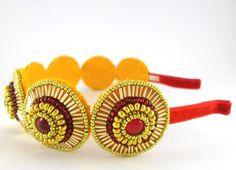 Zlato a rubín Čelenka je zhotovena z červených čirých kabošonů obšitých kvalitním zlatým rokajlem Preciosa a zlatými čípky. Kovový základ čelenky je potažen červenou sametovou stuhou. Vhodný doplněk na ples či na oživení účesu při dalších společenských akcích.