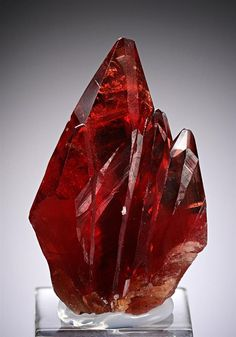 A gemmy, cherry-red Rhodochrosite crystal, 3.5 cm tall, with five smaller part-crystals around its prism faces and aligned in parallel growth to the c-axis.  This specimen is a terrific example of this classic material from the N'Chwaning Mines at Kuruman in the Kalahari Manganese Field, South Africa.